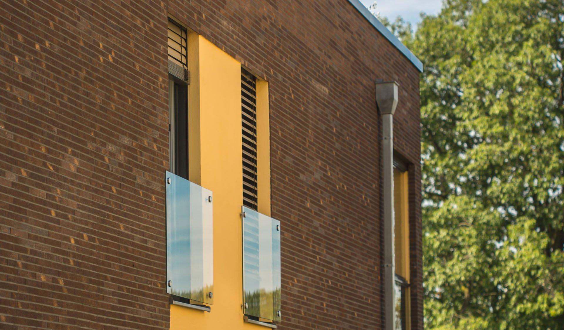 Hauswand mit Fenstern und Jalousien